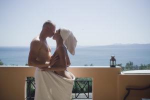 par i kärlek insvept i en handduk, kramar och kysser på balkongen.
